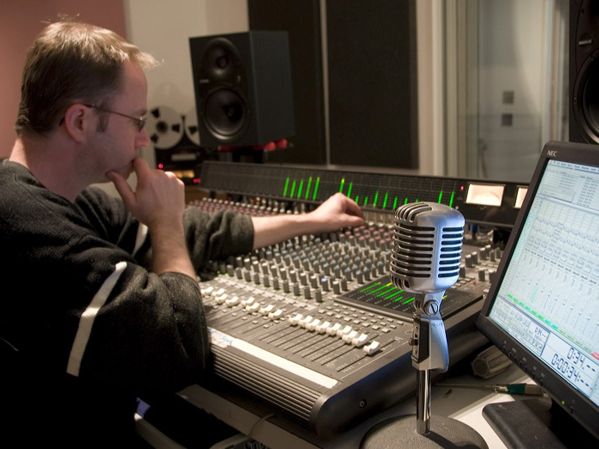 Sound engineer shown in studio seated at mixing board